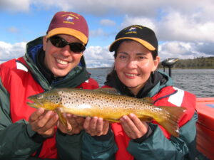2 people holding a wild brown trout on a Tasmanian lake